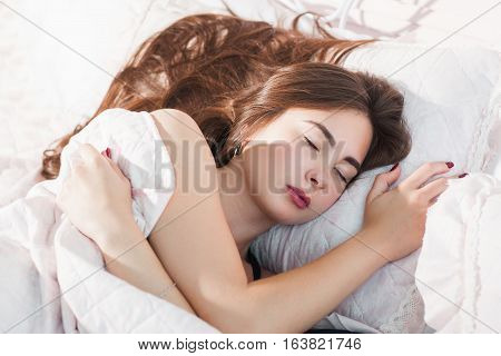 Beautiful woman sleeping in cozy bed. Young girl having rest on expensive qualitative bed linen. Good dream, relax, luxury, pleasure concept