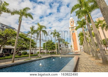 Beautiful view of old Clock Tower with a pool and palm trees at in Tsim Sha Tsui, Kowloon, near Victoria Harbour, Hong Kong.