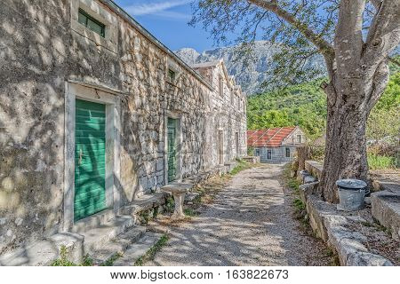 Typical house in Tucepi old village in the slope of a mountain Biokovo. Tree shadow texture on the facade.