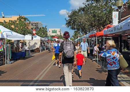 SARASOTA FLORIDA - NOVEMBER 19 2016: Vendors and shoppers at the Sarasota Farmers Market in fall. This vibrant event occurs downtown on Lemon Avenue and State Street every Saturday from 7 AM to 1 PM.