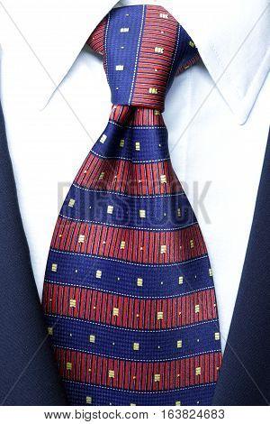 official dress code - classic blue suit, red tie knot, white shirt, closeup, official wear detail,