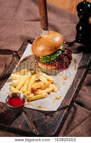 juicy and flavored. Close up of big tasty burger and French fries standing on a wooden tray while being served with pita and sauce in restaurant.