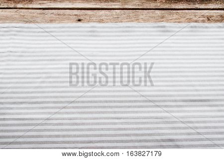 Fabric background, kitchen napkin on wooden table. Horizontal gray stripes on white material, free space, void