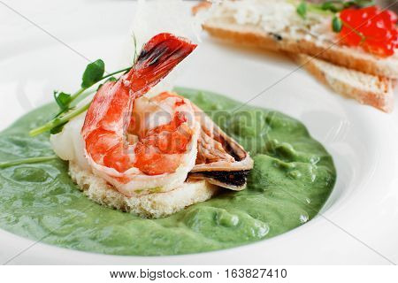 Broccoli cream soup with seafood close-up. Tasty spinach soup with shrimp and mussel, served with red caviar canape. Mediterranean cuisine, healthy food, restaurant menu concept