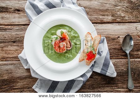 Spinach cream soup with shrimp and mussel flat lay. Top view on plate with portion of broccoli puree with seafood. Mediterranean cuisine, healthy food, restaurant menu concept