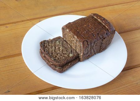 Sliced wholegrain black bread lies on white plate on brown wooden surface. Photo closeup