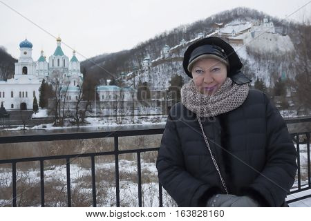 Church Sviatohirsk Lavra. Cloudy day in January. The woman on the waterfront