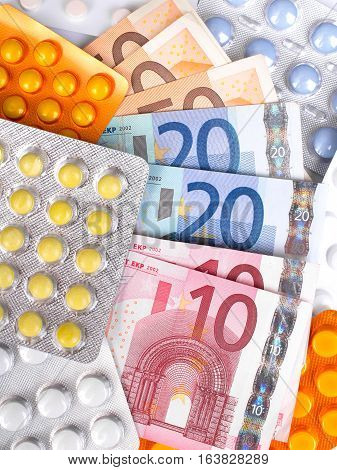 Photo of a Euro money bills and colorful pills.