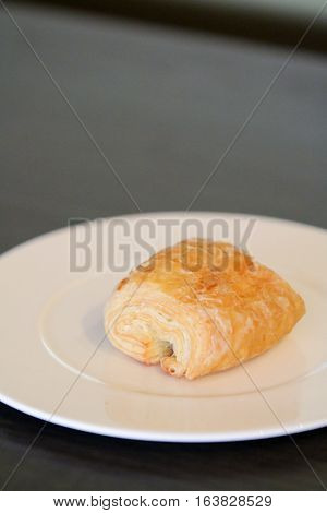 Danish with chocolate stick filled pastry cake on white plate