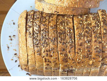Sliced wholegrain bread lies on white plate, top view closeup