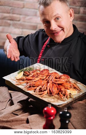 ook what I have. Overjoyed cheerful handsome man demonstrating a tray full of crayfishes while spending time in restaurant and having dinner.