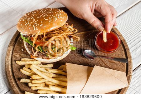 Man dip french fries into red sauce top view. Male hand tasting fried potato with ketchup, classic burger menu. Traditional american cuisine, lunch time, fast junk food concept