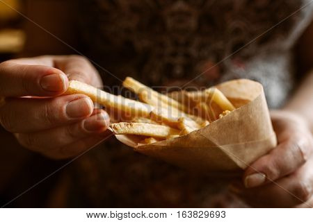 French fries eating close-up. Unrecognizable woman taking fried potato from paper pack. Junk fast food, lunch time, snack, favorite recipe concept