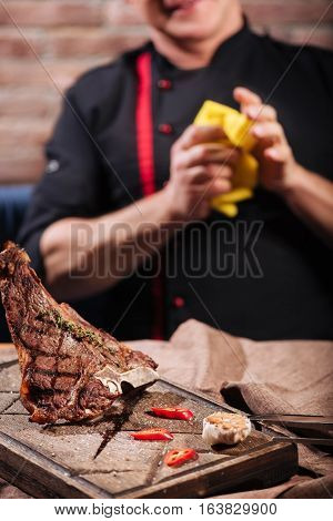 My perfect meal. Close up of steak and a man standing in restaurant before having dinner.
