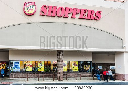 Fairfax, USA - November 30, 2016: Shoppers grocery store facade and sign with people and sale banners