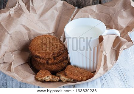 a Mug with milk and oatmeal cookies wrapped in paper edge