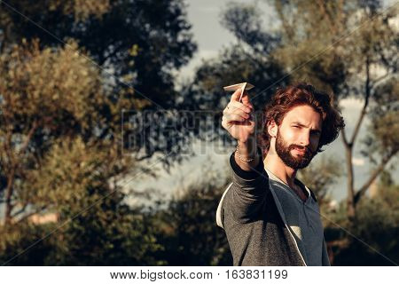 Man aiming paper airplane to camera free space. Bearded stylish guy launching paper plane at nature. Leisure, entertainment, open-air game, rest, pastime concept