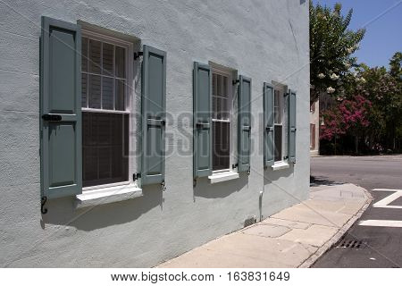 Three windows with shutters of a historic colonial structure in downtown Charleston, South Carolina