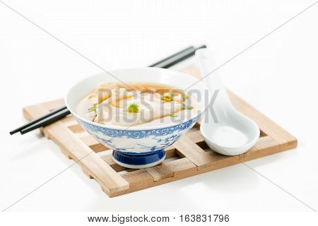 Single bowl of hot wonton soup on a wooden trivet.