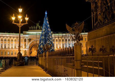 Christmas tree on the background of the arch of the General Staff on Palace Square. Saint-Petersburg, Russia. In the foreground fence and pedestal of the Alexander Column.