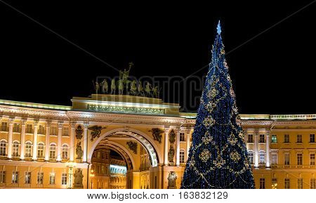 Christmas tree on the background of the arch of the General Staff on Palace Square. Saint-Petersburg, Russia. Christmas tree decorated with glowing blue lights.