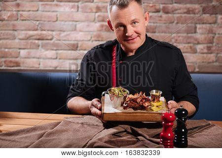Perfect cooking. Glad delighted handsome man eating bacon and salad while sitting in restaurant and enjoying the meal.