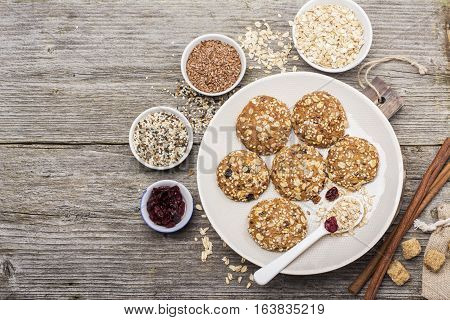 Multigrain Oatmeal cookies with flax seeds, sesame seeds, dried cranberries, cane sugar on a ceramic dish on a wooden background. Top view