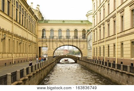 SAINT-PETERSBURG RUSSIA - JULY 14 2012: Hermitage bridge and excursion boat with tourists on canal. Hermitage bridge was built in 1763 year.