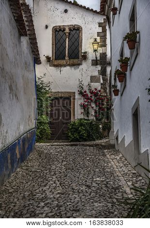 Portugal Obidos - urban village and the castle of the same name with the fortress. Cobbled stone streets stairs and an abundance of decorative flowers .