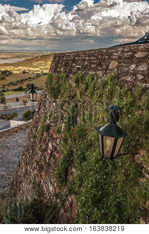 Portugal Monsaraz. Medieval castle wall of rough stone overgrown with grass . On the wall of an old lantern. Clear sunny day on a bright blue sky white clouds float .
