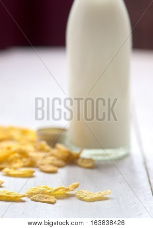 bottle milk and corn flakes on wooden table