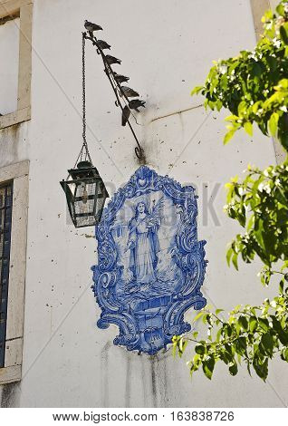 Portugal Lisbon . Image of Saint Louise on the facade of the house made of azulezhu - as the Portuguese call their world famous ceramic tile .