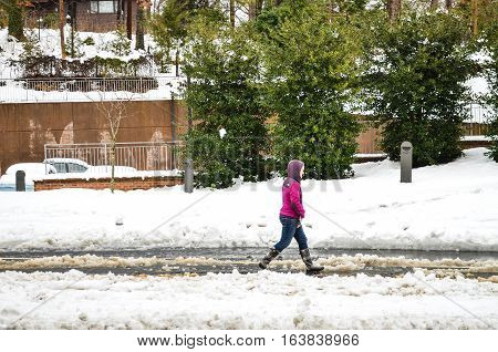Charlottesville, USA - March 6, 2013: Woman walking on snow covered street after storm on University of Virginia campus