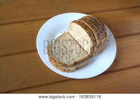 Sliced wholegrain bread with sesame lies on white plate on brown wooden table. Photo closeup