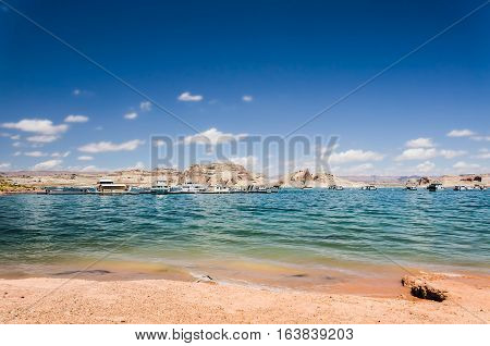 Sunny day at Lake Powell with boats and canyons in clear water