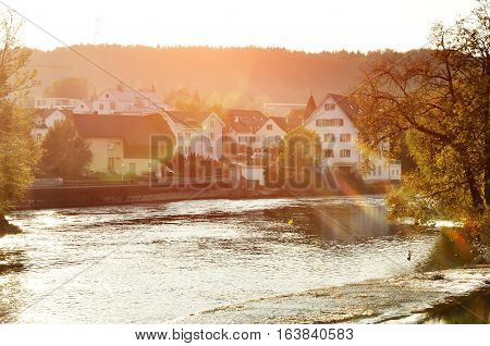 Bremgarten canton Aargau Switzerland - scenic view of Reuss river and houses with sloping roof at sunset