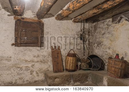 Basement of an old house with wooden beams and wall with humidity, antique household items, carboy demijohn, stewpot, plank, Wicker basket, pulley with chain, wooden window locked