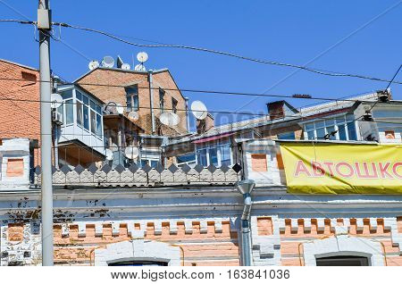 Kiev, Ukraine - May 25, 2013: Satellite TV dishes antennas on houses in downtown with sign