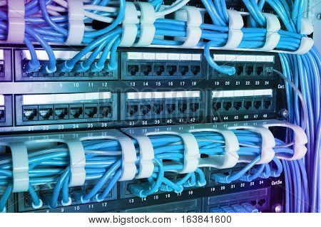 Network switch and blue ethernet cables in server room. Patch cords connected to router in data center. Horizontal technology background with gradient