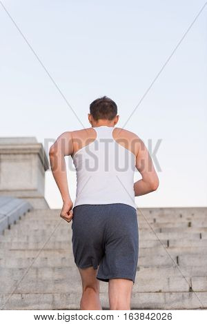 Back of young fit man running up steps outside during workout