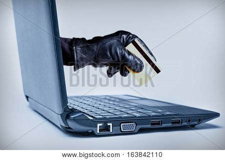 A gloved hand reaching out through a laptop holding debit or credit card signifying a cybercrime or Internet theft. poster
