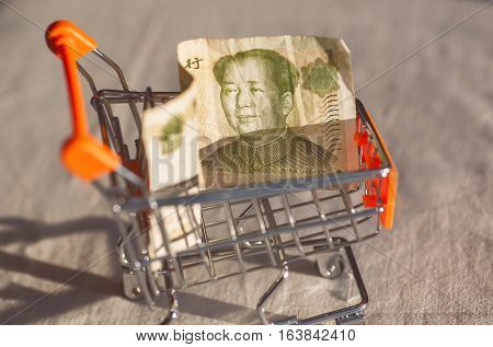 Supermarket cart with a banknote of Chinese Yuan and face of Mao, as a symbol of modern international economy
