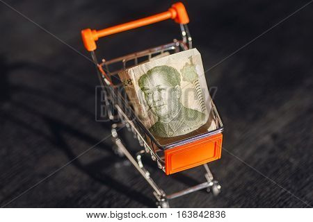 Market cart with a banknote of Chinese Yuan and face of leader Mao, as a symbol of the modern international economy