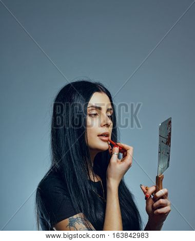 Pretty gothic girl with chopper over gray background
