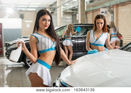 Sexy curly long haired blondes in fromula one style tops and mini skirts posing with pompons near car at carwash
