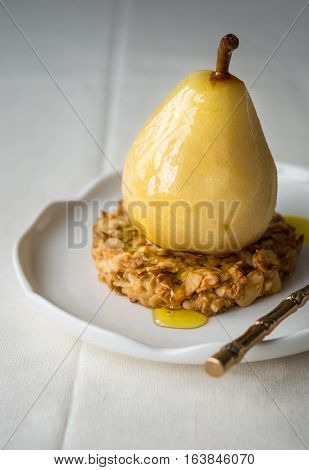 Poached pear in saffron sugar syrup over an oat cookie