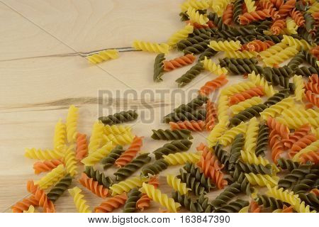 Medley of varieties of rotini pasta on wooden table