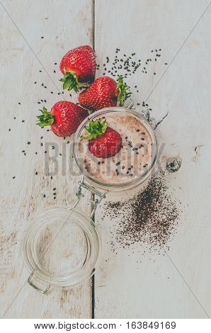 Homemade yogurt in a jar with strawberry seeds and cacao. Dessert with strawberries on a white wooden background. Fresh juicy strawberry with yogurt. Directly above. Top view. Vertical.