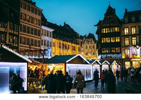 STRASBOURG FRANCE - DEC 20 2016: Famous Christmas Market with Place de la Cathedrale with tourists and locals in front of Notre-Dame Cathedral and iconic maison Kammerzell at dusk