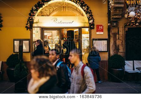 STRASBOURG FRANCE - DEC 20 2016: Woman entering French Restaurant through main festive gate during Christmas Holidays in French city of Strasbourg Maison Kammerzell